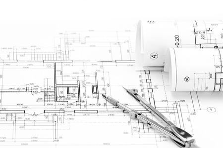 compas de dibujo: rolls of architectural blueprints and house plan with drawing compass Foto de archivo