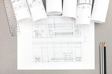 architectural hand-drawn sketch with blueprint rolls on desktop, top view Stok Fotoğraf