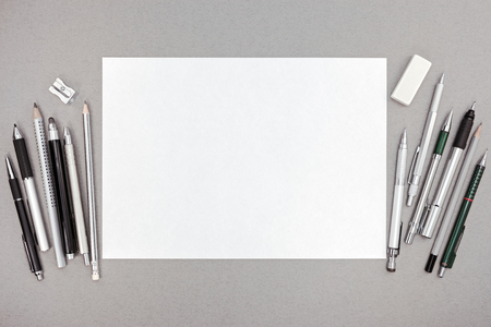 hoja en blanco: espacio de trabajo de diseño con la hoja de papel en blanco y varias herramientas de dibujo, vista desde arriba