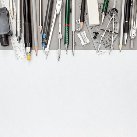compas de dibujo: hoja de papel en blanco con plumas y lápices, compás, transportador de ángulos dibujo, goma de borrar, sacapuntas, vista desde arriba Foto de archivo