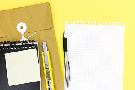 utility knife: envelope, notepad, empty sheet of paper, pen and utility knife on yellow desk