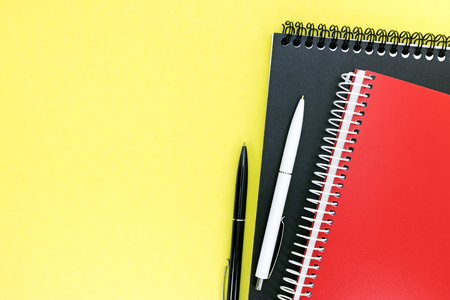red and black notebooks and ballpoint pens on yellow desktop background