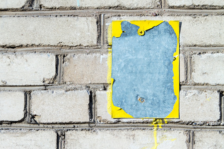 peeledoff: metal plate with peeled-off yellow paint on a brick wall