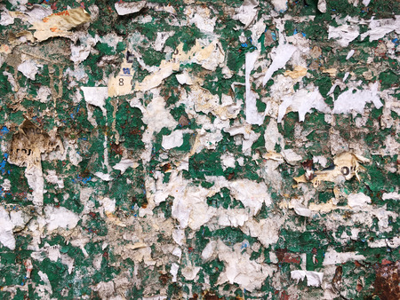 torn metal: torn advertisement on green metal wall  background