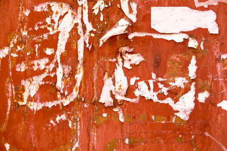 torn advertisement on red metal wall as background