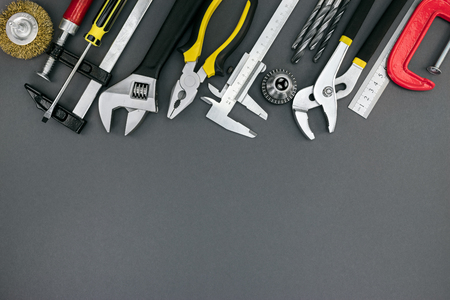 pliers and adjustable wrenches, ruler, clamp, vernier caliper on desk, hand tools top view
