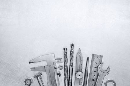 proportional: vernier caliper, drills, bolts, pliers and screws on grey scratched background