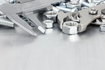 vernier caliper: various hand tools including vernier caliper, slip-joint, screws on scratched metal background