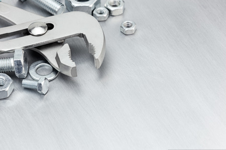 fastening objects: pliers, screws and bolts of different size for manual work on scratched metal background Stock Photo