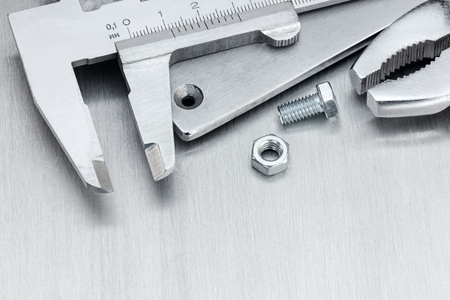 vernier caliper: vernier caliper and pliers on scratched metallic background, macro view