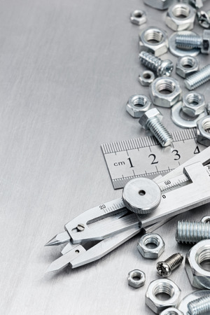 proportional: proportional divider, ruler, screws and bolts on metallic scratched shiny background