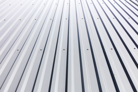 corrugated steel: corrugated steel cladding with rivets on roof of industrial building Stock Photo