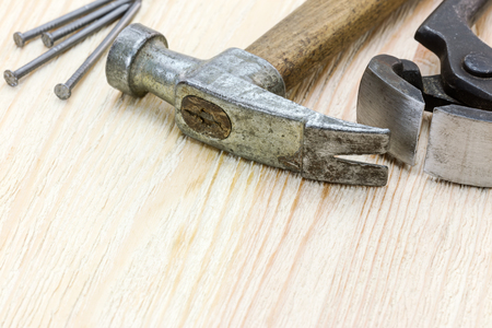 hammer and nails: hammer, nails and pincers on wooden board background. tools and instruments for repair closeup.