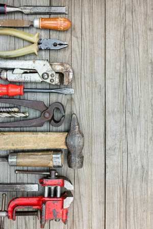 vice grip: old working tools and instruments including hammer, clamps, screwdrivers and other on wooden grey background