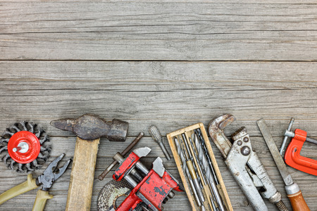 vice grip: set of old various working tools on grey wooden boards background