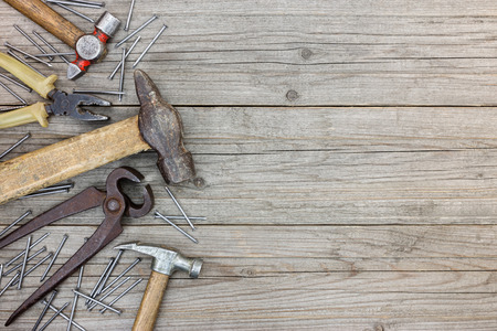 pincers: old tool set of hammers, pliers, pincers and nails on grey grunge wooden boards background