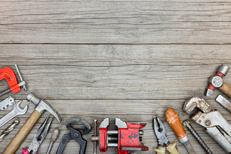 vice grip: old grungy tool set including hammers, drills, pliers, wrenches and clamps on gray wooden boards background