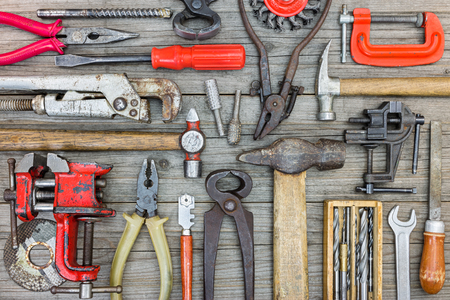 vice grip: collection of various tools, instruments and accessories for house renovation and construction on grey wooden background