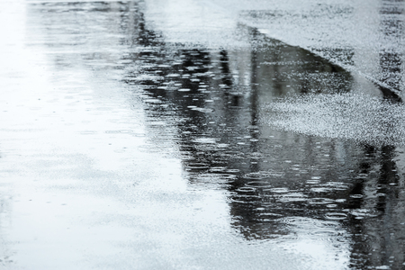 reflection: raindrops rippling in puddles. street road during rainy day.