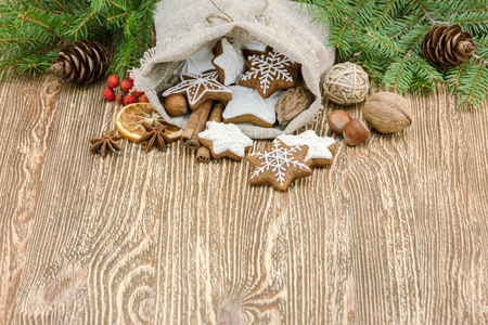 christmas homemade gingerbread cookies in small gift bag on wooden background with fir tree branches