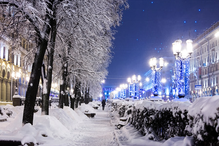 winter city street with trees and benches covered in snow and lamp posts decorated with christmas lights