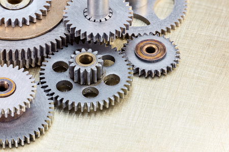 copper texture: different industrial cogwheels on scratched brass background closeup
