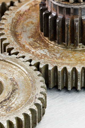 antique factory: old rusty weathered cogwheels for industrial machinery macro view