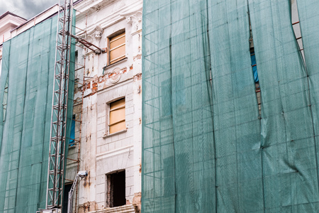 old house facade under renovation wrapped in a green net for safety