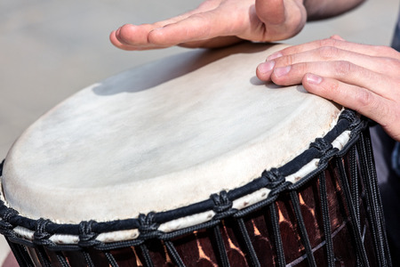 street talented musician playing african drum djembe outdoors. closeup of mans hands.