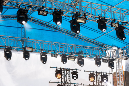 spotlights equipment mounted under roof of on outdoor stage for illumination during concert Stock Photo
