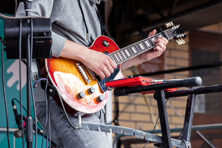 an entertainer: young male musician playing electric guitar during city rock fest Stock Photo