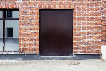 empty warehouse: closed metal doorway painted brown on red brick wall background