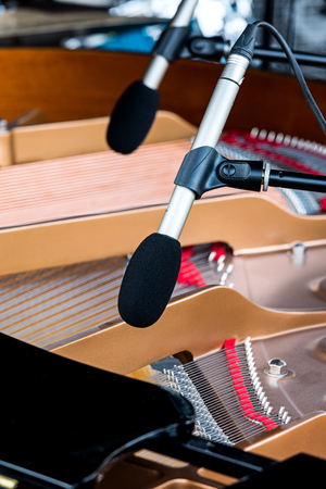 octave: professional microphones above grand piano with selective focus on one of them