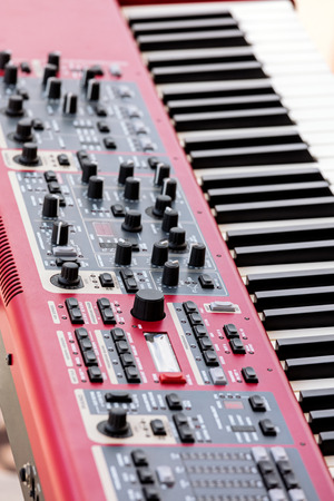dept: keys electronic synthesizer. audio sound mixer with buttons and sliders. shallow dept of field.