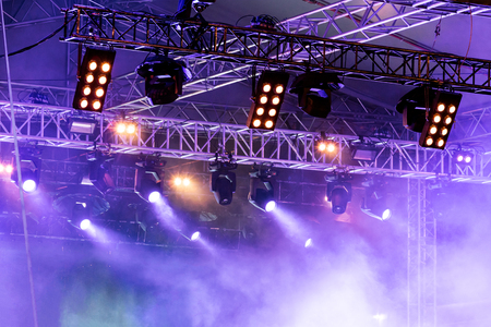 smoky stage illuminated with blue spot lightning system during rock concert