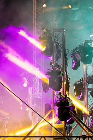 spotlight system mounted on stage. concert lightning effect in the darkness.  Stock Photo