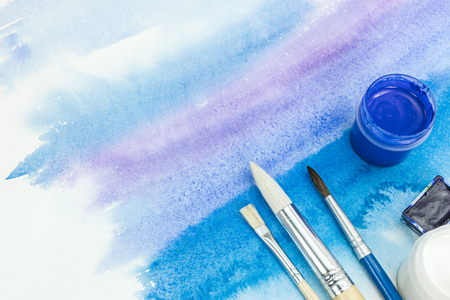 set of paints and paintbrushes on abstract watercolor hand drawn background