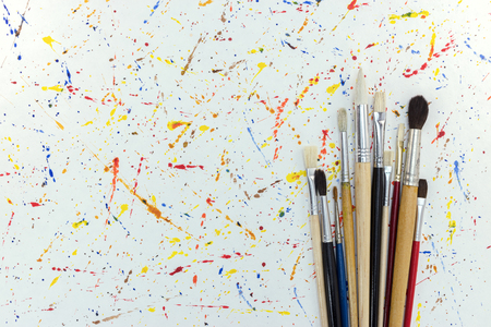 various sizes of paintbrushes on white paper with watercolor blobs background