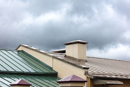 gable home renovation: new metal roofs of old houses wet after the heavy rain
