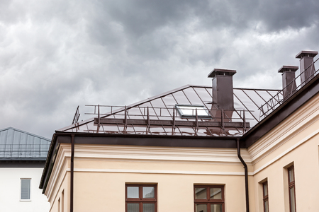 gable home renovation: house with brown metal wet roof, chimneys and skylights during rain Stock Photo