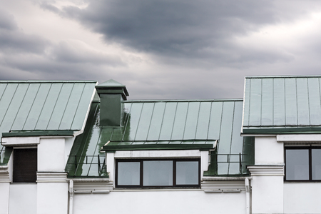 gable home renovation: grey metal roof with windows during the rain against dark cloudy sky