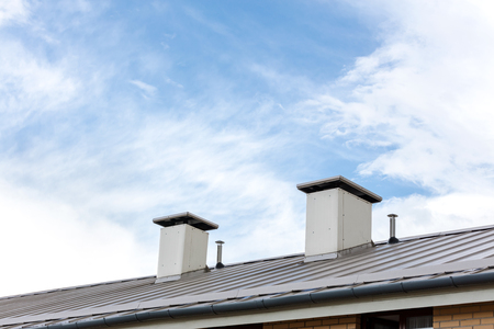 gable home renovation: wet metal roof with chimneys after rain on blue cloudy sky background Stock Photo