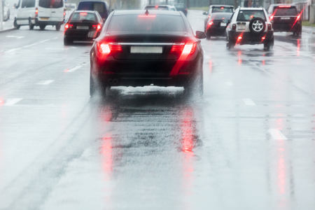 rainy road. driving cars on a wet street with splashing water in motion blur.