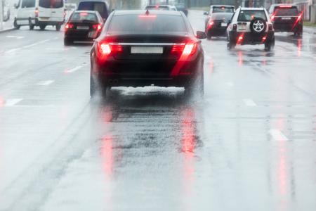 regenachtige weg. auto's rijden op een natte straat met spatwater in beweging vervagen.