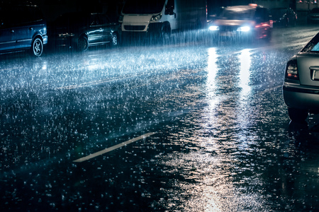 car in motion with switched on headlights driving during heavy rain