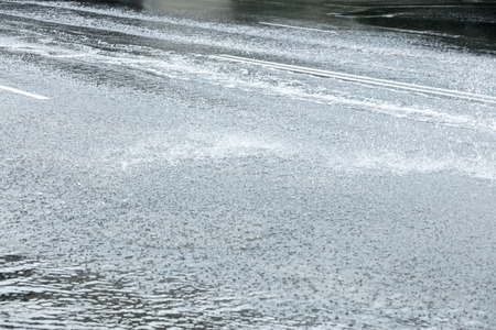 background made from heavy rain and cars driving on flooded road