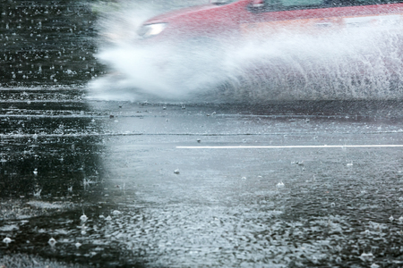 car in motion on flooded road. city during rainy day. Stock Photo