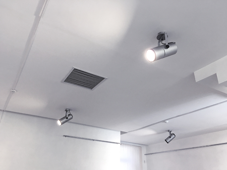 exhibition ceiling light fixtures. bright halogen spotlights on exhibition ceiling. Stock Photo