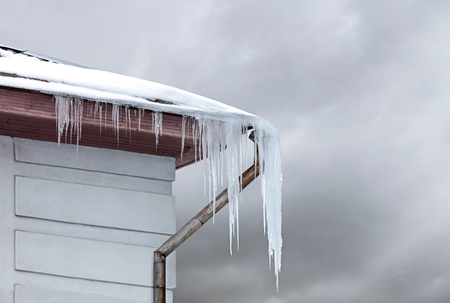 icicles hanging dangerously down from the roof covered with snow