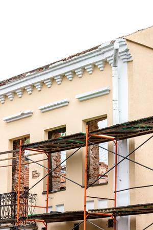 old historical building under restoration, part covered by scaffold